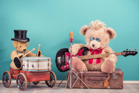 Retro Teddy Bear toys with play bass guitar and sitting on old luggage, golden microphone, bear in cylinder hat playing the drum. Rock or metal music concept. Vintage nostalgia style filtered photo