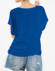 Woman wearing blue t-shirt and short rip jeans with copy space in back side isolated on white background