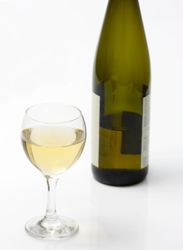glass of white wine and a bottle isolated on white