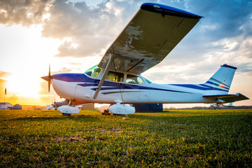 Small private airplanes on the airfield against the backdrop of a colorful sunset