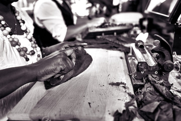Closeup of woman hands making cigar from tobacco leaves. Traditional manufacture of cigars..Demonstration of production of handmade cigars. Hands rolling dried and cured tobacco leaves. bw photo