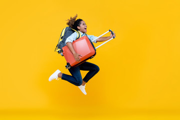 Excited African American woman tourist woman with backpack and luggage jumping