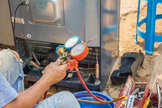 repair refrigerator job with pressure gauge , technician vacuum system refrigerator at maintenance shop.