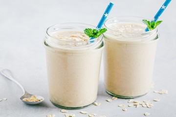 Banana oats smoothie or milkshake in glass mason jars on a stone background