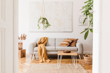 The stylish boho compostion at living room interior with design gray sofa, wooden coffee table, cube, basket and elegant personal accessories. Honey yellow pillow and plaid. Cozy apartment. Home decor Fototapete