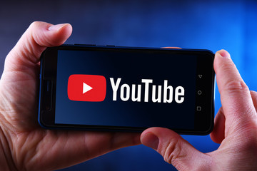 Hands holding smartphone displaying logo of YouTube