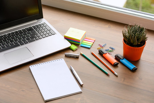 An open notebook for notes, pencils, markers, a pen, a pot with cactus, a notebook and paper clips on a wooden background (office desk).