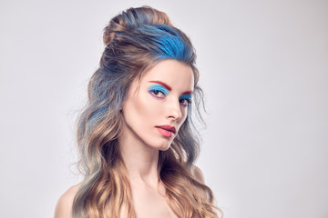 Wall Mural - High Fashion. Beautiful woman with art paint makeup, creative Dyed hairstyle. Gorgeous blonde girl with styling wavy hair, healthy skin. Young model girl, fashionable make up. Creative Beauty portrait