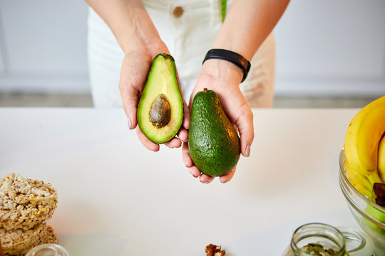 Young happy woman holding avocado for making salad in the beautiful kitchen with green fresh ingredients indoors. Healthy food and Dieting concept. Loosing Weight