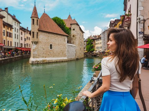 Brunette girl with long hair and blue skirt stands on the canal promenade in Annecy in France, everywhere flowers and bicycles