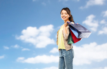 sale, outlet and consumerism concept - happy asian young woman with shopping bags over blue sky background