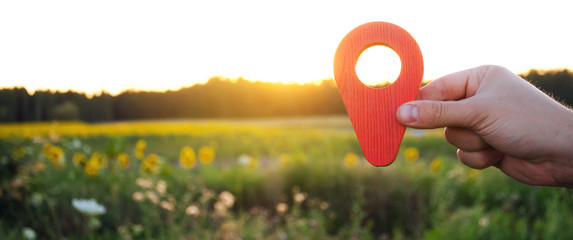 A hand is holding a red location marker in the sunset background. The concept of tourism and travel. Navigation and exploration. Destination. Holiday, vacation. Buying building land. Selective focus