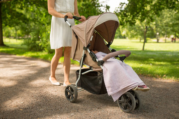 family, motherhood and people concept - mother with child sleeping in stroller walking at summer park