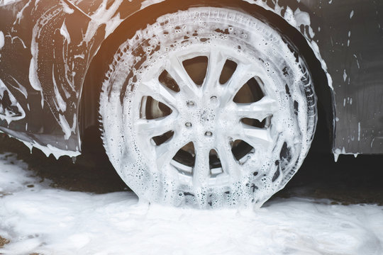 car wash with active foam soap. cleaning wheel tire. commercial cleaning service concept.