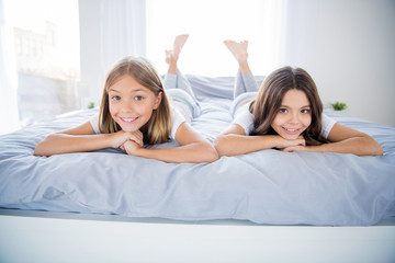 Close up photo of charmign cute kids blonde brunette hairstyle fellows have free time lie bed room indoors