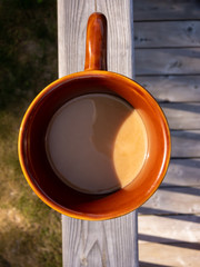 cup of coffee on wooden railing, shot from above