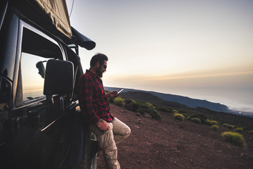 Adventure explorer traveler man use cellular phone with internet connection in wild mountain place during travel excursion with off road black car and tent on the roof - free people concept Fototapete