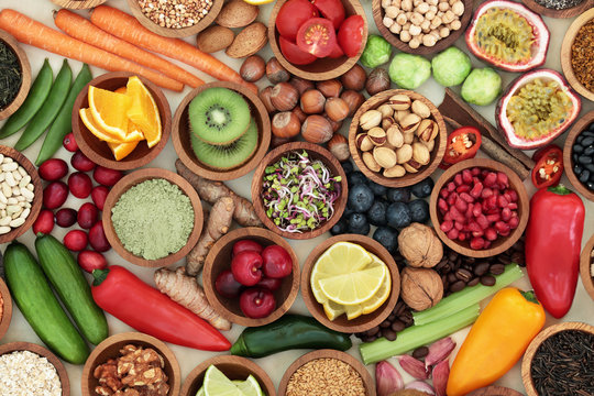 Health food for clean eating concept with fresh fruit, vegetables, supplement powders, legumes, grain, seeds, nuts, herbs and spices. High in antioxidants, anthocyanins, vitamins and dietary fibre.