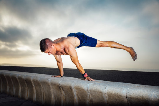 fitness, sport, training, calisthenics and lifestyle concept -  Young man training on the street doing straddle planche