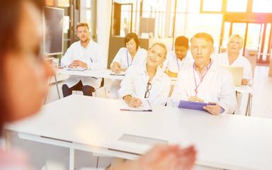 Pharmareferent vor Gruppe Ärzte beim Seminar