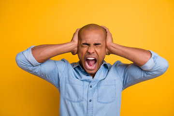 Close-up photo of angry irritated guy holding palms on ears do not want to listen to loud music from neightbors isolated vivid background