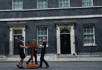 Workers carry a podium outside 10 Downing Street ahead of the speech of Theresa May on her last day in office as Britain's Prime Minister, in London