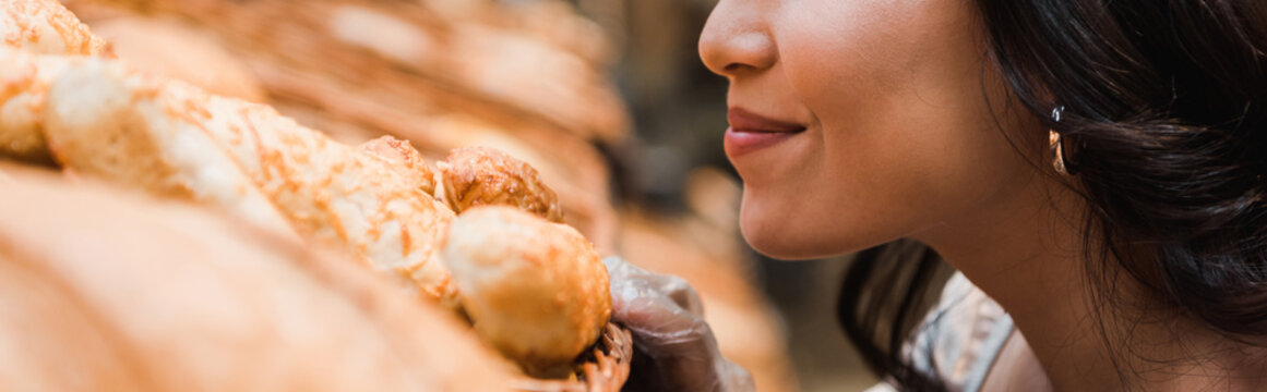 panoramic shot of cheerful woman smiling while smelling bread in supermarket