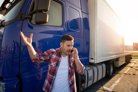 Truck driver talking on the phone and arguing in front of the truck trailer. Trucker transportation problems. Problems on the road.