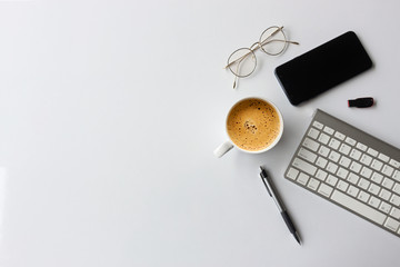business concept. top view of office desk workspace with smartphone, pen, keyboard, glasses and hot coffee cup on white table background. over light