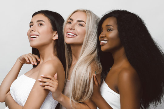 Beauty photo of three smiling multiracial women with different types of skin: Caucasian, African american and Asian girls, isolated over white background. Beautiful  young women with natural make-up.