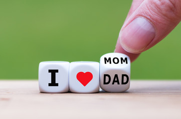 """Hand turns a dice and changes the expression """"I love mom"""" to """"I love dad"""" or vice versa."""