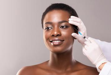 Beautiful black woman making plastic surgery procedure for face