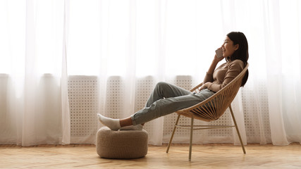 Girl Resting in Armchair and Talking on Phone