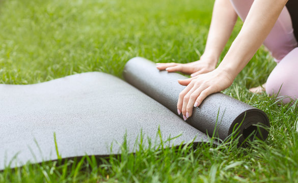 Young woman rolling yoga mat before or after practicing outdoors