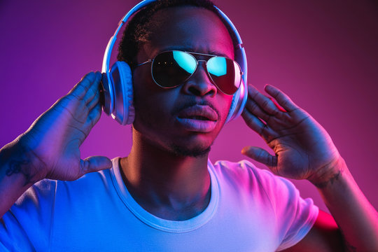 Young african-american man's listening to music in headphones in neon light on gradient background. Male portrait. Concept of human emotions, facial expression, summer holidays or weekend, hobby,