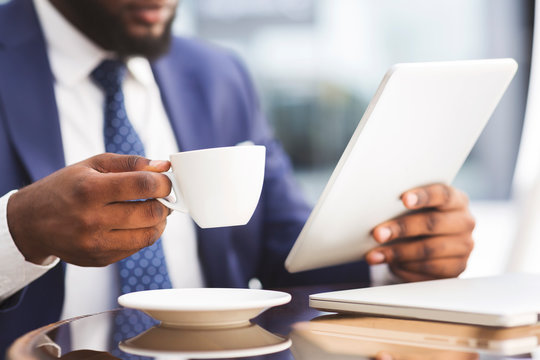 Unrecognizable African American Businessman Having Coffee While Working On Tablet