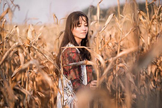 Portrait of a beautiful brunette girl in an autumn corn field