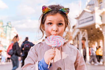 Little girl with big lollipop is playing and having fun in the park. Weekend entertainment for the child. A beautiful and happy child. Copy space.