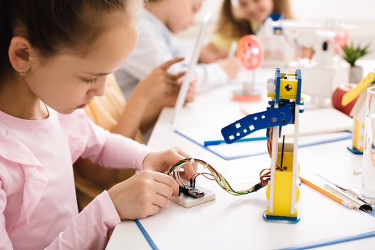Girl building robot, working with wires in class