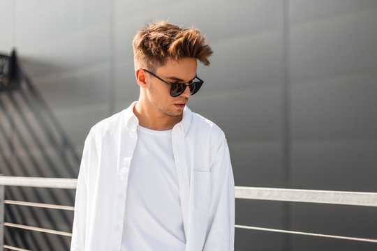Stylish young man model in vintage white shirt in trendy sunglasses with a hairstyle stands near a gray building on a sunny day. European hipster guy on the street. New summer collection menswear.