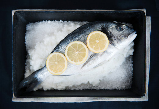 Overhead view of fish with sliced lemon in a container