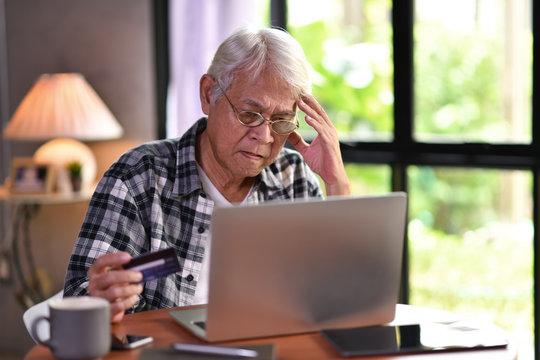 Asian senior man looking confuse when using credit card for online shopping