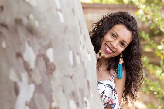 Mujer joven latina de piel morena y cabello largo y rizado, sonrie asomándose desde detrás de un árbol