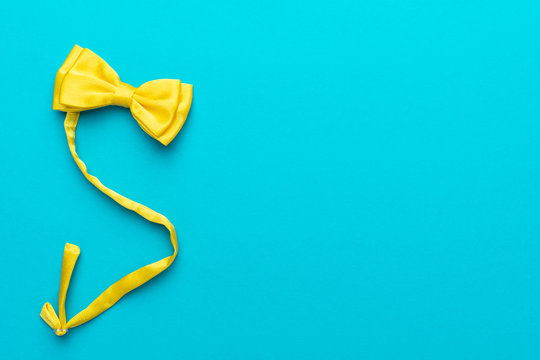Top view photo of yellow satin bow tie over turquoise blue background with copy space. Minimalist flat lay image of pre-tied vivid bow tie. Left side composition of men's accessory.