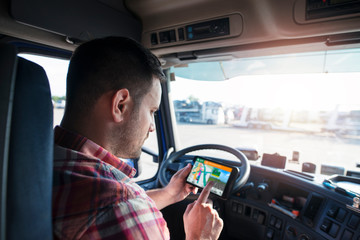 Professional middle aged trucker using truck gps navigation to transport and deliver goods to the destination. Transportation services. Wall mural