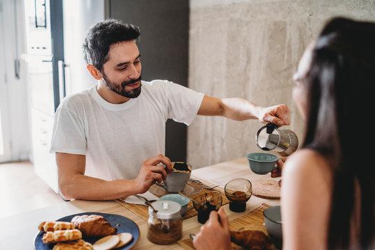 Couple having breakfast at kitchen table
