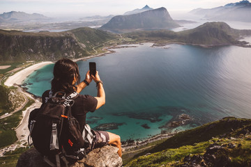 Man with a cellphone sitting in a rock taking photos of the view