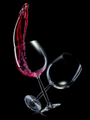 Set of empty glasses for red wine with splashes in a row isolated on black background.