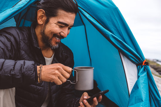 Man with a mug and a cellphone sitting at a camping tent by the sea