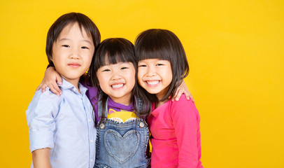 Portrait group of young happy little asian girls boy on yellow background with copy space. Education teampower brainstorm, childhood lifestyle back to school together concept